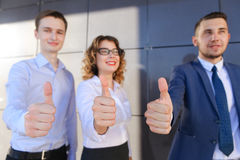 Three beautiful young people showing thumbs up, laughing, smilin Royalty Free Stock Images
