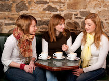 Three beautiful young students in bar. Three beautiful young students waiting drinking  coffee and having a debate in coffee shop Stock Photos
