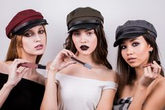 Three beautiful young women with bright makeup and caps represent cosmetics product, keep in the hands of different shades of lips royalty free stock images