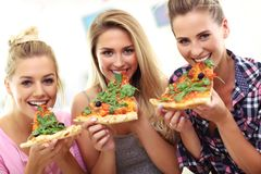 Three beautiful young women eating pizza at home stock photography