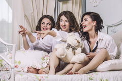 Three beautiful young women friends chatting in the bedroom in Stock Photo