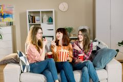Three beautiful young women friends at home eating popcorn sitting on gray sofa together and laughing. Home women party.  royalty free stock image