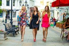 Three beautiful young women girlfriends walk on a summer street Stock Photos