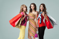 Three beautiful young women holding shopping bags Royalty Free Stock Photography