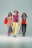 Three beautiful young women holding shopping bags Stock Photography