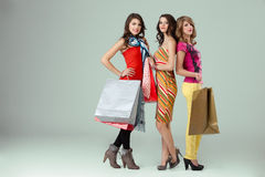 Three beautiful young women holding shopping bags Royalty Free Stock Images