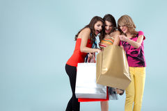 Three beautiful young women holding shopping bags Stock Images