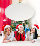 Three beautiful young women lying in front of a Christmas tree Stock Photo