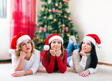 Three beautiful young women lying in front of a Christmas tree Stock Images