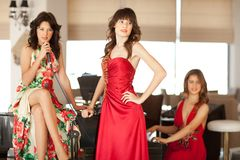Three beautiful young women at a piano Royalty Free Stock Images