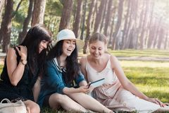Three beautiful young women rest and joying at summer park with smartphone. Group of happy international people.  stock photography