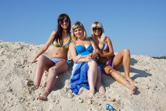 Three beautiful young women  on a sand-pit Stock Images