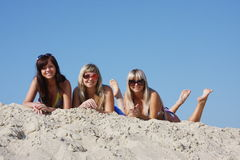 Three beautiful young women  on a sand-pit Royalty Free Stock Image