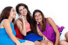 Three beautiful young women with a smart cell phone. Royalty Free Stock Photos