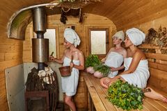 Three girls relaxing in sauna stock photography