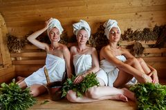 Three girls relaxing in sauna. Three beautiful young women in towels realxing in wooden sauna. inside shot with natural light Royalty Free Stock Photography