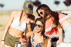 Three beautiful young women using mobile phone on road trip. Stock Photography