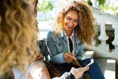 Three beautiful young women using they mobile phone in the street. Stock Photography