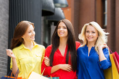 Three beautiful young women walking in the city center Royalty Free Stock Photos