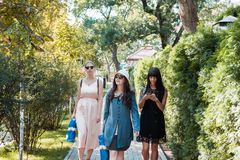 Three beautiful young women walking in summer park after shopping. Group of international people.  royalty free stock photo