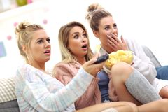 Three beautiful young women watching tv at home Royalty Free Stock Photos