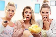 Three beautiful young women watching tv at home Stock Photos