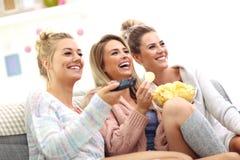 Three beautiful young women watching tv at home Stock Photo