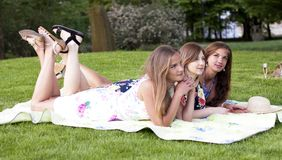 Three ladies in picnic. Having fun. Three beautiful ladies having picnic. Laying on blanket. Legs lifted and crossed. Summer dresses, sun tan, long hair royalty free stock photography