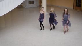 Three beauty strolling through the empty room. One of them wore a sexy dress, two other girls dressed flying dresses of. Three fashion girls from the higher stock footage