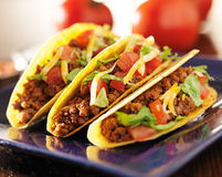 Three beef tacos with cheese, lettuce and tomatoes Stock Images
