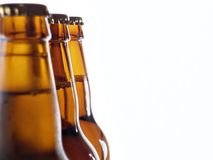 Three beer bottles. Upper part of three beer bottles isolated on white royalty free stock photography