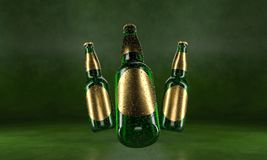 Three beer bottles standing on a rustic green table. Beer mock up. Wet beer bottles withgolden labels and water drops stock photo