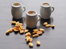 Three beer mugs and a snack with nuts on a wooden table. stock images