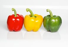 Three bell peppers. In the color of a traffic light in front of a white background Stock Image