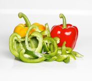 Three bell peppers. One cut in small pieces in the color of a traffic light in front of a white background Royalty Free Stock Photos