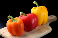 Three Bell Peppers on a cutting board. Orange, Red, and Yellow Bell Peppers on a wooden cutting board, against a dark background Stock Photo