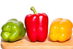 Three bell peppers - green, red and yellow on a cutting board Royalty Free Stock Photo