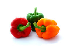 Three Bell Peppers. Red, green and orange bell peppers on an isolated white background Stock Images