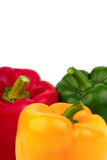 Three bell peppers - red, yellow and green. On a white background Royalty Free Stock Image
