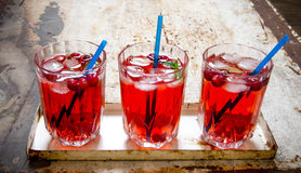 Three berry cocktails with ice and mint leaves on the old rustic background . Royalty Free Stock Image