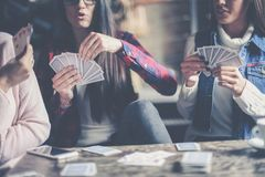 Three best friends in cafe playing together game cards. royalty free stock images