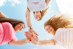 Three best friends looking down and holding hands. Oudoors Royalty Free Stock Photography