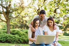 Three best friends in park enjoying and typing on laptop. Happy friends in park using laptop and enjoying the day Royalty Free Stock Photography