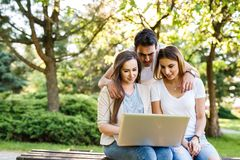 Three best friends in park enjoying and typing on laptop. Happy friends in park using laptop and enjoying the day Royalty Free Stock Images