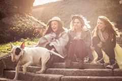 Three best friends sitting on the stairs. Young girls with their pets stock image