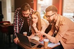 Three best friends are standing near table with computer on it and looking to the screen. One of them is pointing on the. Screen. The other two are listening to Royalty Free Stock Image