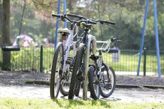 Three bicycles for all family. Are parking in an English park during their owners have a walk. Two bicycles for parents, mom and dad, and small one is for a kid Royalty Free Stock Photos