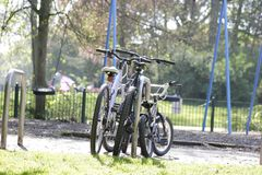 Three bicycles for all family. Are parking in an English park during their owners have a walk. Two bicycles for parents, mom and dad, and small one is for a kid Royalty Free Stock Photography
