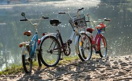 Three bicycles on a beach. Three colorful bicycles parked against water on the beach, family travel Stock Photos