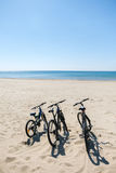 Three bicycles are on the beach on sea background Royalty Free Stock Photo